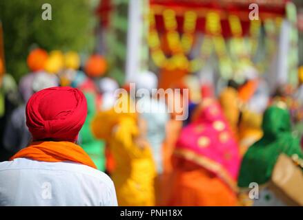 La religione sikh uomo con turbante rosso durante una parata esterna e più persone Foto Stock