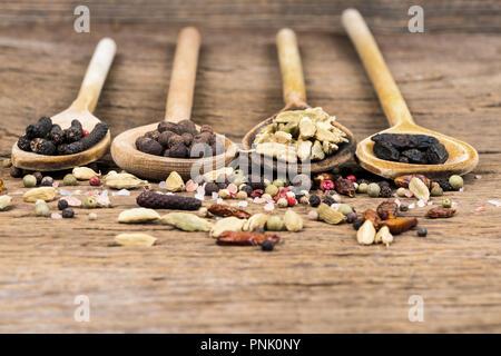 Primo piano di legno quattro cucchiai di cottura in una fila con varie spezie esotiche su un rustico in legno con sfondo spazio copia Foto Stock