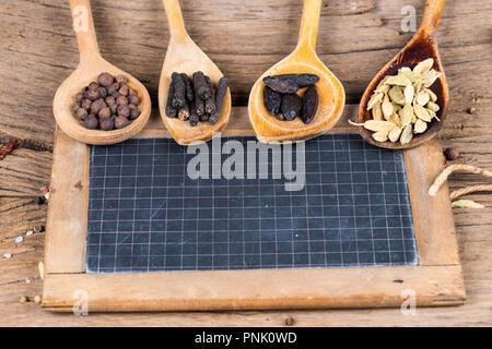 Primo piano di legno quattro cucchiai di cottura con varie spezie esotiche e una vecchia lavagna di ardesia per la marcatura su un rustico sfondo di legno Foto Stock