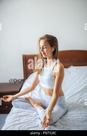Yoga donna ascoltando musica durante la mattina yoga pratica sul letto. Foto Stock