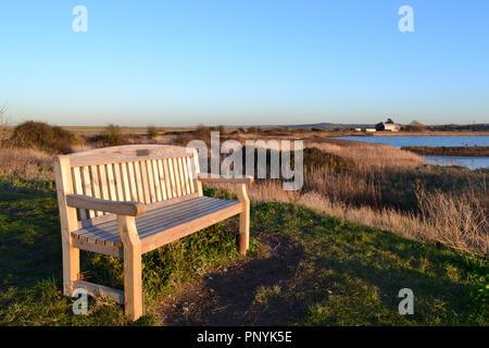 Un sedile rivolto verso ovest come il sole tramonta su Cliffe paludi nel Kent, Inghilterra, su una giornata invernale e. Verso la fine di dicembre 2017