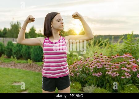 Persone, alimentazione STAMINA, forza, salute, sport, concetto di fitness. Outdoor ritratto sorridente ragazza adolescente flettendo i suoi muscoli, sfondo verde prato sun