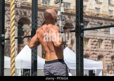 Atleta fitness muscolare maschio modello tirando verso l'alto sulla barra orizzontale in una palestra. Primo piano della forte atleta facendo pull-up sulla barra orizzontale Foto Stock