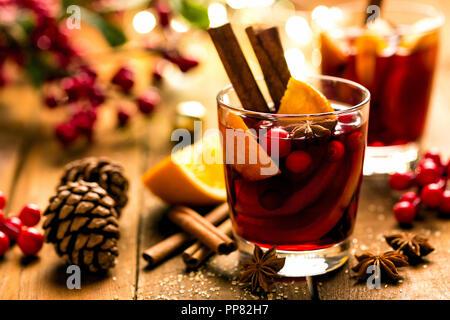 Natale rimuginassero vino rosso con le spezie e le arance in un rustico in legno tavolo. Tradizionale bevanda calda a Natale Foto Stock
