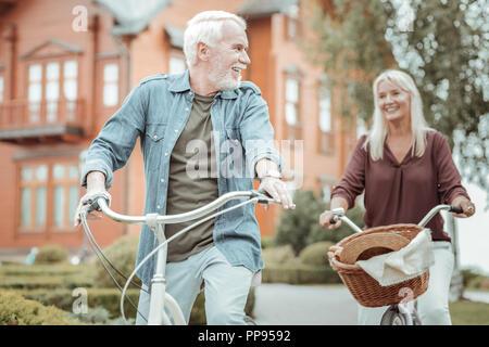 Positivo coppia felice con le loro biciclette mentre si cammina Foto Stock