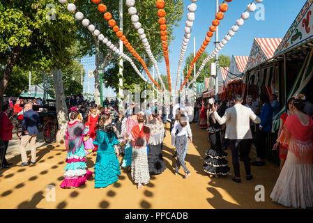 Lo spagnolo le donne con colorati abiti di flamenco di fronte marquees, Casetas, Feria de Abril di Siviglia, in Andalusia, Spagna Foto Stock
