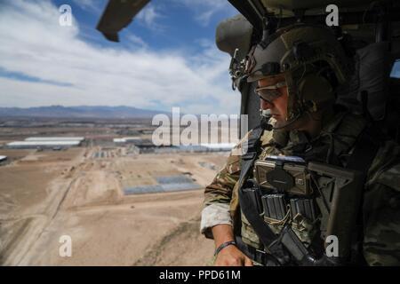 Un U.S. Le forze speciali soldato, assegnato al decimo delle forze speciali Gruppo (airborne), si affaccia sulla città di Las Vegas da un UH-60 Blackhawk elicottero mentre è volato fuori al Nevada Test e campo di addestramento prima di eseguire un addestramento al combattimento esercizio vicino alla Nellis AFB, Nevada, Agosto 28, 2018. Lo scopo di questa formazione è quello di dare le Air Force gli studenti che passano attraverso il giunto di attacco terminale corso Controller, un realistico combat mission-lo scenario di addestramento.