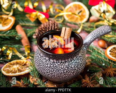 Natale vin brulé con cannella, arancione e anice stellato in un vaso in ceramica con decorazioni d'inverno. Foto Stock