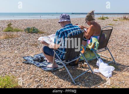 Paio di persone seduti su sedie da spiaggia in estate a Littlehampton, West Sussex, in Inghilterra, Regno Unito. Foto Stock