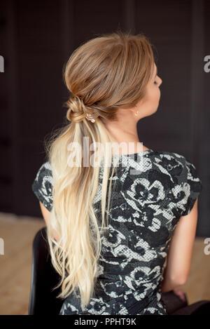 Irriconoscibile vista posteriore della donna acconciatura. A mezza lunghezza vista posteriore della donna con cintura slim e capelli lunghi che indossa in stile sportivo abbigliamento Foto Stock