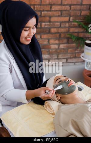 Giovane donna con maschera facciale di fango Foto Stock