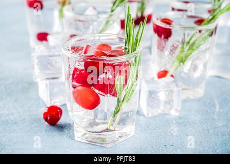 Natale o Capodanno inverno cocktail a base di mirtillo palustre con rosmarino, il liquore gin tonic, sulla luce blu sullo sfondo di calcestruzzo con cubetti di ghiaccio, frutti di bosco freschi e