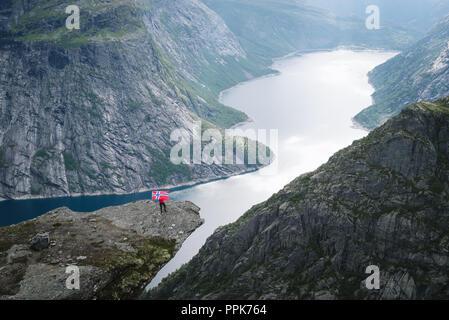 Trolltunga - cliff roccia sopra il lago Ringedalsvatnet in Norvegia. Turistico con bandiera norvegese Foto Stock