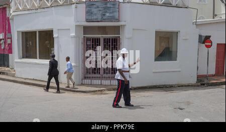 Funzionario di polizia dirigere traffico per un funzionario di polizia i funerali nell'angolo di Queen Street e Church Street, Speightstown, Barbados Foto Stock