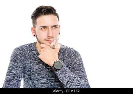 Scettici moderni giovani brunette uomo con orologio e canto un mento guarda pensieroso nel futuro - isolato in uno sfondo bianco Foto Stock