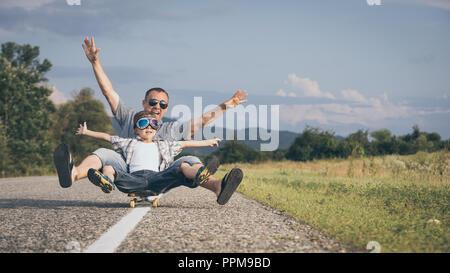 Padre e figlio giocando sulla strada al giorno. Le persone aventi il divertimento all'aperto. Concetto di famiglia amichevole.
