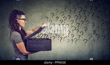 Donna felice con molte domande alla ricerca di una risposta Foto Stock
