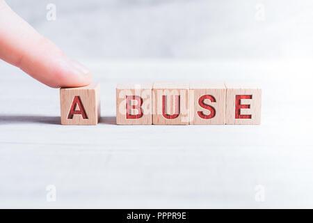 La parola abuso formata da blocchi di legno e disposti da un maschio di dito su un tavolo bianco