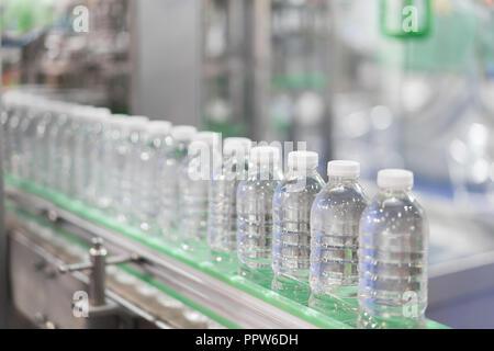 Cancellare le bottiglie di acqua il trasferimento sul Sistema di trasporto a nastro. Industriali e di fabbrica con la tecnologia della macchina concept.