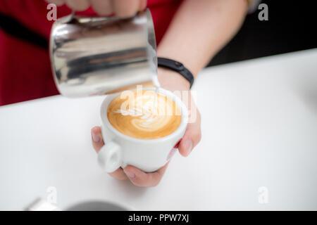 Barista versa una tazza di latte e caffè crea una bella immagine Foto Stock