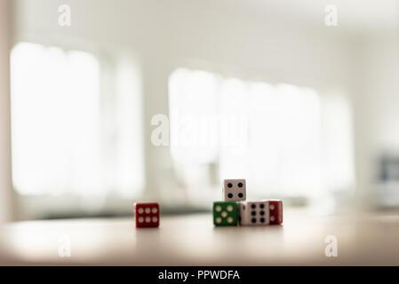 Dadi di gioco impilati sulla scrivania in un ufficio luminoso. Foto Stock