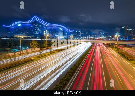Chengdu, nella provincia di Sichuan, in Cina - Settembre 27, 2018: semaforo sentieri sul Tianfu avenue di notte illuminata con il nuovo secolo centro globale in background Foto Stock