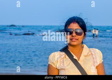 Ritratto di bellezza del volto femminile con pelle naturale. Giovane bella donna pone sulla spiaggia sfondo. Foto Stock