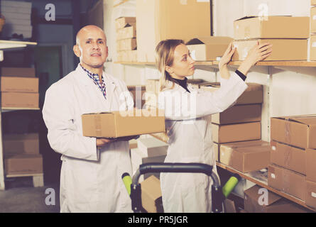Giovani femmine e positivo maschio adulto carrello di trasporto delle scatole di cartone in deposito Foto Stock