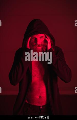 Uomo in luce rossa tenendo la sua testa Foto Stock