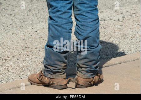 Stivali da cowboy e jeans blu di un uomo seduto sul vecchio