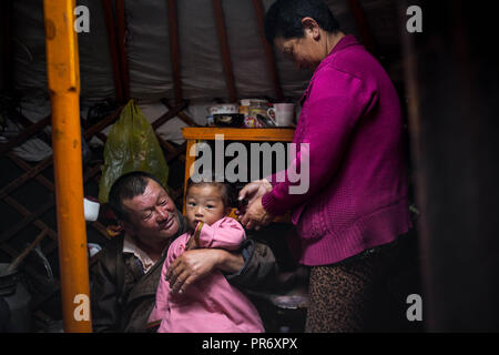 Nonni visto holding e prendersi cura della loro figlia piccola nel corso di un inizio di mattina dentro la loro yurt vicino alla città di Uyanga in Övörkhangai Provincia, Mongolia meridionale. Foto Stock