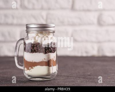 Cioccolata calda mix a mason jar. Mix fatti in casa a base di cacao, latte secco, zucchero, scaglie di cioccolato e marshmallows. Natale e vacanze inverno budget-friendly Vacanze doni idea. Spazio di copia Foto Stock