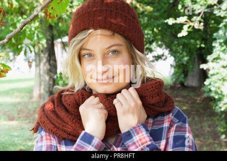 ... Giovane donna indossa cappello di lana e sciarpa outdoor guardando la  telecamera Foto Stock 0e80144e9c3d