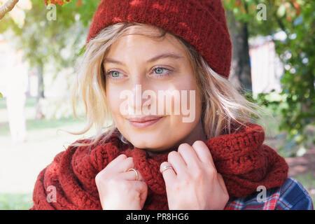 Giovane donna indossa cappello di lana e sciarpa per esterno Foto Stock a56e324c0a8d