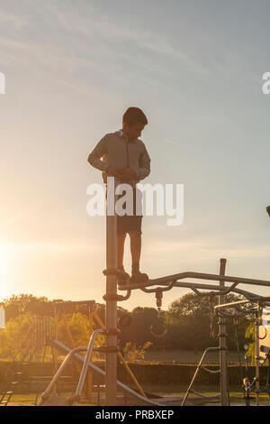 Regno Unito,Surrey,Cheam Park,Boy-10 anni , riproduce solo sul parco giochi Foto Stock