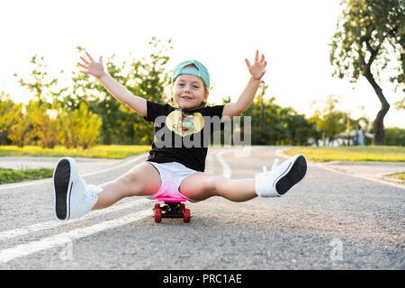 Equitazione per bambini skateboard in estate park. Bambina di imparare a cavalcare skateboard. Active outdoor sport per la scuola e per la scuola materna i bambini. I bambini lo skateboard. Preschooler su longboard. Kid pattinaggio Foto Stock