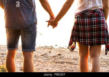 Coppia giovane in ama camminare nel parco di autunno tenendo le mani guardando il tramonto Foto Stock