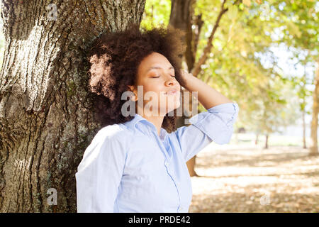 Outdoor ritratto di felice bella african american woman in natura, femmina in magliette blu Godetevi giornate estive, poggiando su albero nel parco, occhi chiusi Foto Stock