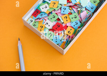 Matita e punti di domanda in una scatola di carta su sfondo giallo. Concetto di immagine. Close up. Foto Stock