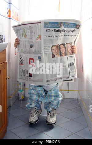 Un momento di pace. Piccolo ragazzo lettura broadsheet giornale sul wc. Foto Stock