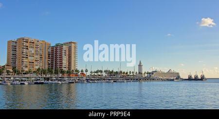 Barche a vela di fronte a grandi edifici di appartamenti e di torre faro nel porto di Malaga, Spagna Foto Stock
