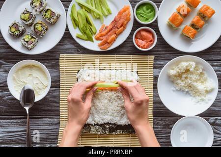 Ritagliato colpo di persona la cottura delizioso sushi roll con salmone, avocado e cetrioli Foto Stock