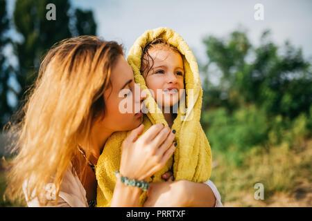 Madre figlia di copertura con asciugamano dopo il nuoto in acqua Foto Stock