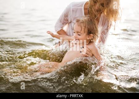 Felice madre e figlia nuoto insieme nel fiume Foto Stock