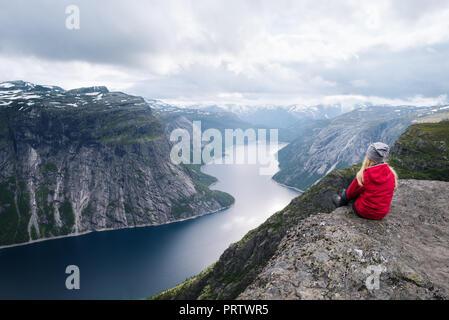 Majestic Trolltunga - uno di Norvegia la maggior parte vista spettacolare. Ragazza in giacca rossa si siede sulla roccia e guarda al lago Ringedalsvatnet Foto Stock