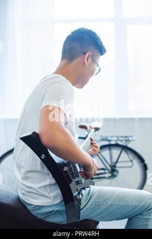 Vista laterale del uomo asiatico giocando unplugged chitarra elettrica a casa