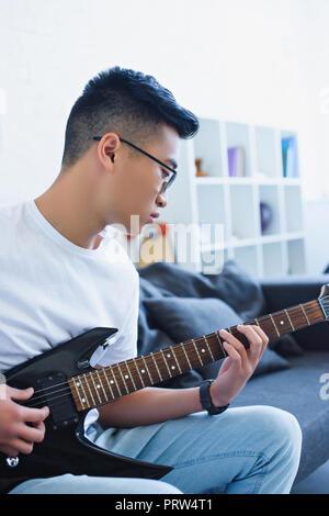 Bel uomo asiatico suonare la chitarra elettrica a casa