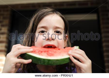 Closeup ritratto di un felice giovane ragazza mancanti di denti frontali di mordere in una grande fetta di anguria a casa all'aperto Foto Stock