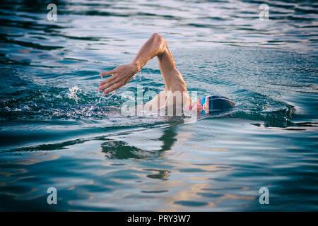 Nuotatore respirazione durante il nuoto crawl in mare al tramonto Foto Stock