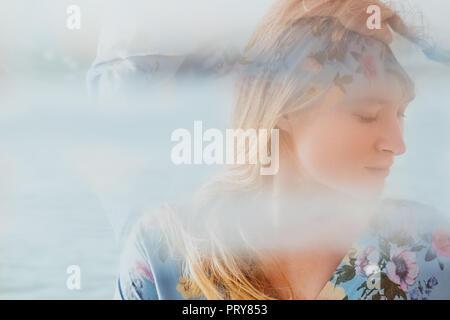 Close-up ortrait di una giovane bella aggraziato e naturalmente donna bionda in vestito blu con il mare in background Foto Stock